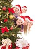 Groupez les personnes dans le chapeau de Santa par l'arbre de Noël. Photo libre de droits
