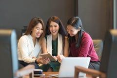 Groupez trois femmes se réunissant dans un café causant à chaque othe Image stock