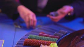 Groupier verzamelt en sorteert gokkenspaanders op Roulettelijst stock videobeelden