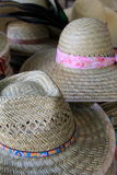 Grouping of straw hats on table. Grouping of colorful straw hats on table at outdoor flea market Stock Photo