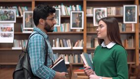 Groupmates Meet in Library. Two intelligent students in glasses meet in college library, holding books while talking, indoor shot before packed bookshelves stock video