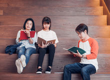 Groups of asian teenage students reading book together at university stair library.  royalty free stock photography