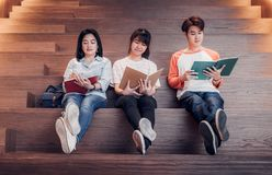 Groups of asian teenage students reading book together at university stair library.  royalty free stock photos