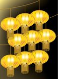 Groups of golden lanterns hanging on strings on black background Royalty Free Stock Images