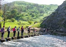 Groups of people crossing Dovedale River Walk royalty free stock image