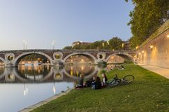 Groups of people enjoying the sunset. TOLOUSE, FRANCE - OCTOBER 3 2014: Groups of people enjoying the sunset near one of the beautiful bridges crossing the stock photography