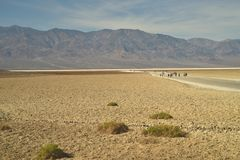 People walking out onto salt flats in Death Valley. Groups of people traveling and visiting are walking out to the salt flats at Bad Water in Death Valley Royalty Free Stock Images
