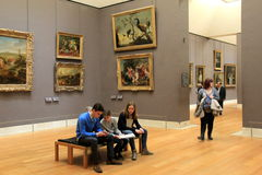 Groups of sightseers wandering through a room of masterpieces,The Louvre,Paris,2016. Groups of sightseers either sitting on long wood benches or wandering Stock Images