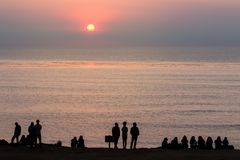 Groups of Sillhouetted people sit and stand along cliffs watching sunset royalty free stock photos