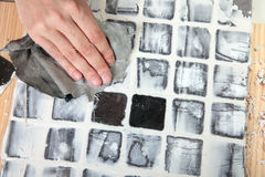 Grout. Worker applies grout at grey tiles Stock Photo