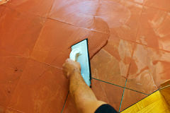 Grout is applied. A tiler carries on floor tiles on the grout. grouting of tiles Royalty Free Stock Image