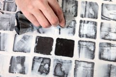 Grout. Worker applies grout at grey tiles Royalty Free Stock Photo
