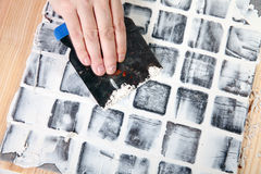 Grout. Worker applies grout at grey tiles Royalty Free Stock Image