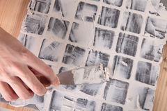 Grout. Worker applies grout at grey tiles Stock Photos
