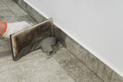 Grouting ceramic tiles. Tilers filling the space between tiles using a rubber trowel Stock Photos