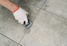 Grouting ceramic tiles. Royalty Free Stock Images