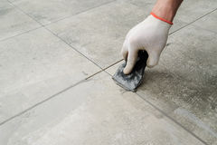 Grouting ceramic tiles. Tilers filling the space between tiles using a rubber trowel Stock Photo