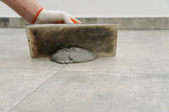 Grouting ceramic tiles. Royalty Free Stock Image