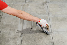 Grouting ceramic tiles. Royalty Free Stock Photo