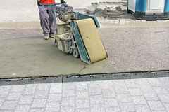 Grouting compound street. Worker with machine, grouting compound street paved with bricks Stock Images