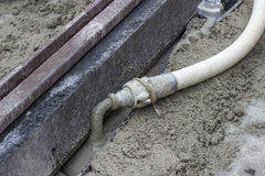 Grouting mortar and tram track laying 3. Mortar from grout mixer and delivery system, grouting pump used to settle the grout into the joints. Grouting mortar and Royalty Free Stock Images