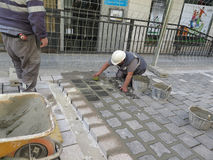 Grouting newly laid road stones Royalty Free Stock Photography