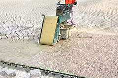 Grouting terraces. Worker with machine, grouting compound street paved with bricks Stock Photos