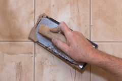 Grouting Tile. Man's hand with grout trowel while working on ceramic tile Stock Photo