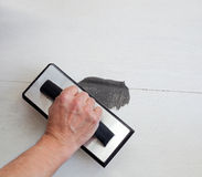 Grouting tiles with rubber trowel man hand Stock Images