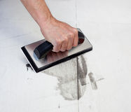 Grouting tiles with rubber trowel man hand. Grouting tiles with rubber trowel and gray cement mortar Royalty Free Stock Photos