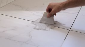 Grouting tiles seams with a rubber trowel.  stock video