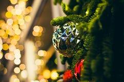 Grov boll för stor silver på julgrancloseupen med gul bokeh arkivfoto