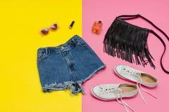 Grov bomullstvill kortsluter, vita gymnastikskor, den svarta handväskan, solglasögon brigham royaltyfria foton