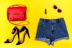 Grov bomullstvillkortslutningar, svarta skor, röd handväska och exponeringsglas ljus yellow för bakgrund trendigt begrepp Royaltyfri Foto