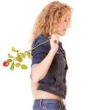Grov bomullstvillmode. Blond flicka för sidosikt i jeans med den röda rosen Royaltyfri Foto