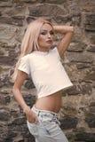 Grov bomullstvillstil Banta, modemodellen med den sexiga buken i tshirt och jeans Banta, modemodellen med långt blont hår och Royaltyfria Foton