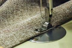 Grov bomullstvilltyg på symaskinen Närbild av sömnadprocen arkivfoto