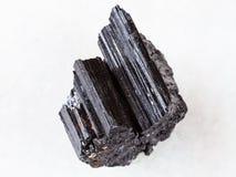 Grov kristall av den svarta tourmalinen på vit Arkivfoton