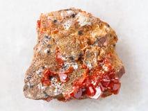 grova kristaller av Vanadinite på stenen på vit Arkivfoto