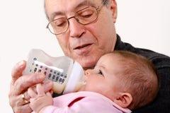 Großvater, der Baby mit der Flasche füttert Stockbilder