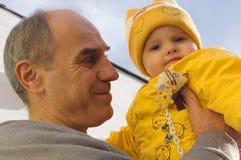 Großvater hält seine Enkelin an Stockfotos