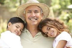 Großvater mit Enkelkindern im Garten Stockfotos