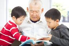 Großvater und Enkelkinder, die ein Buch lesen Stockfotografie