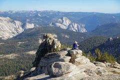 Groveland,加利福尼亚-美国- 2014年7月24日:妇女休息注视在半圆顶和尤塞米提谷 免版税库存图片