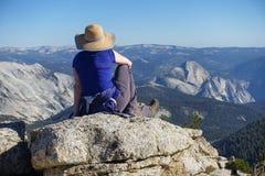 Groveland Kalifornien - Förenta staterna - Juli 24, 2014: En ensam kvinna sitter att se ut över halv kupol, i den Yosemite nation arkivfoto