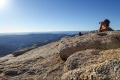 Groveland Kalifornien - Förenta staterna - Juli 24, 2014: Mannen söker med kikare, når han har fotvandrat till överkanten av Mt h arkivfoto