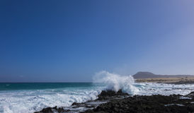 Grovt hav med berget på öar för Corralejo strandkanariefågel Spanien Arkivfoto