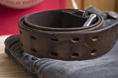 Grovt läderbälte på jeansbakgrund Fotografering för Bildbyråer