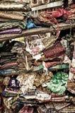 Grovt stapla av kläder på hylla Arkivbild