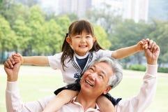 Großväterliche gebende Enkelin-Fahrt auf Schultern Stockbild